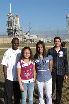 Four students stand in front of the space shuttle and its launch pad