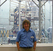 Jim Gealy standing in front of windows with a spacecraft in the background