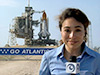 Mary Estacion stands near Launch Pad 39A with Atlantis on the pad before launch.