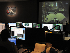 An engineer monitors activities on the large screens at the Space Telescope Operations Control Center.