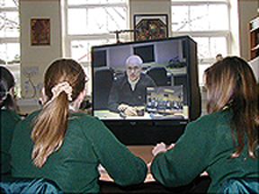 Picture of two students watching a videoconference of a NASA scientist.
