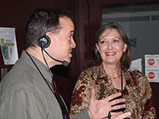 A man wearing a headset speaks to a smiling woman
