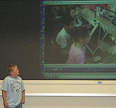 A student stands beside a screen on which students can be seen using a glovebox