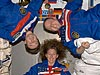 Three astronauts float, with two sideways and one right side up