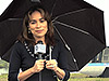 Mary Estacion holds an umbrella in the rain at Kennedy Space Center.