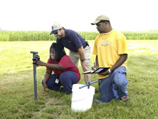 Scientists taking measurements of soil moisture with ground-based sensors