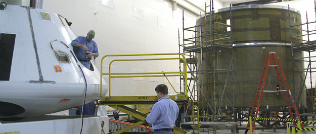 While finishing touches are applied to the MLAS crew module, foreground, the lower sections of the MLAS test vehicle take shape in the background. The separation between the larger boost skirt and the coast skirt is the metallic strip seen just above the ladder.