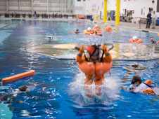 Crew members wear orange launch and entry suits in a large pool