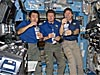 Expedition 19 crew members hold drink bags of recycled water
