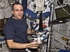 Astronaut Donald Pettit holds a piece of hardware on the space station