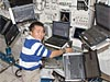 Japanese astronaut Koichi Wakata with five laptop computers near him