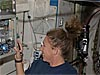 Astronaut Sandra Magnus works with an experiment on a wall of the space station