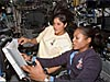 Astronauts Joan Higginbotham and Sunita Williams read a manual about the space station robotic arm