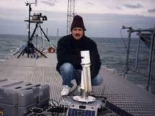 Alexander Smirnov, an AERONET project scientist, is leading a new effort to study marine aerosol particles. In this photo, taken on the coast of North Carolina, Smirnov is posing next to a land-based AERONET sensor. Credit: NASA