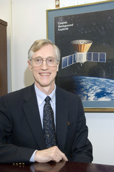 Dr. John Mather sits in front of an artist's depiction of the COBE satellite.