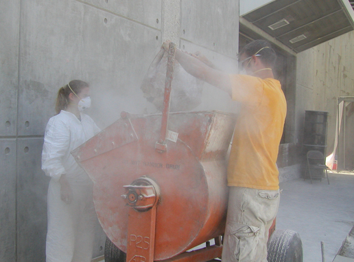 Rover team members fill a mixer with powdered clay and diatomaceous earth.