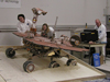 a test rover rolls off a plywood surface into a prepared bed of soft soil