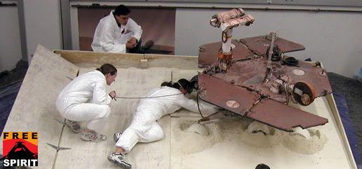 Mars Exploration Rover team members prepare a testing setup for the Spirit rover.