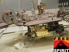 In this view from behind a test rover, the rear wheels of the rover are turned toward the left, and the left-front wheel is turned toward the the right.