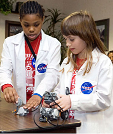 Two students, and a small robot on a table