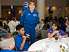 An astronaut talking to students at a table