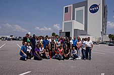 A group of students pose in front of the Vehicle Assembly Building