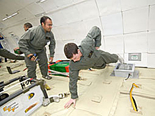 One student watches as another does a one-hand push-up in simulated lunar gravity