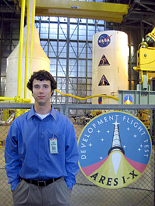Brandon Lojewski standing near spaceflight hardware and a large Ares I-X mission patch