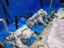 Two astronauts wearing spacesuits underwater