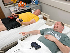 Two bed rest study participants lying in bed and playing a video game