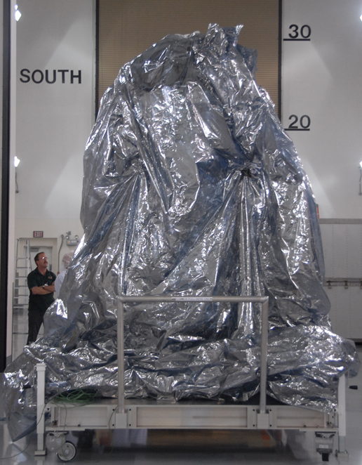 The WISE spacecraft sits with its protective covering.
