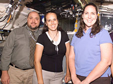 Mike Baine, Cari Goulard and Katie Boyles standing inside a mock-up of the space shuttle flight deck