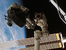 Astronaut on the end of the station robotic arm holds a Control Moment Gyroscope
