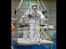 Two astronauts in training spacesuits are lowered into the water