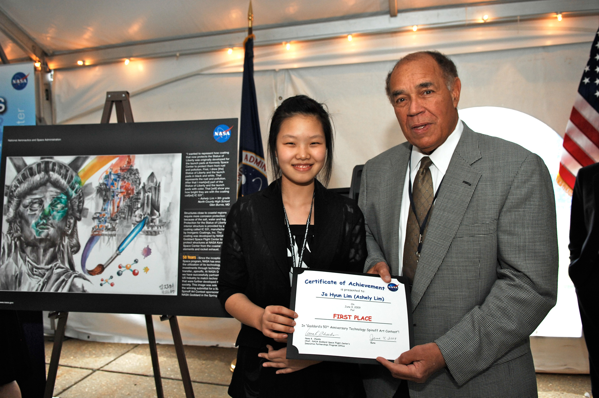 Ja Hyun Ashely Lim is pictured here with her award-winning painting, and Fred Gregory, former NASA Deputy Administrator and former shuttle astronaut. She won the Goddard Celebrates 50 Years of Technology Spinoffs Art Contest