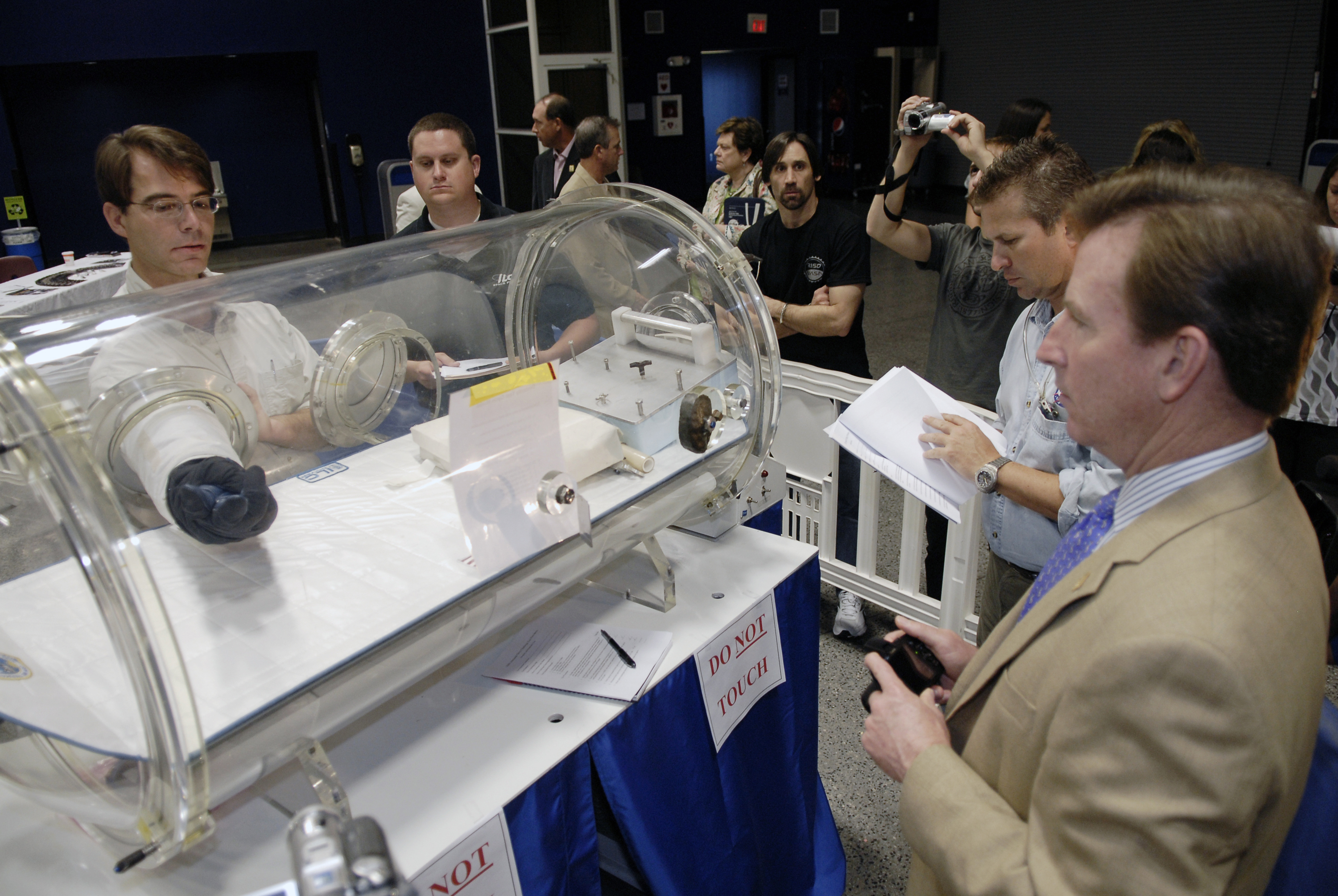 Inventor Peter Homer, left, participates in the dexterity and flexibility test during NASA's 2009 Astronaut Glove Challenge at the Astronaut Hall of Fame near Kennedy Space Center