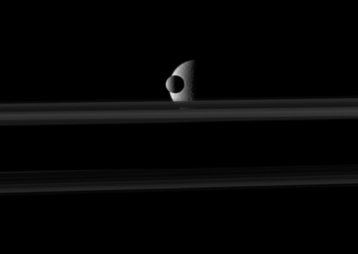The small moon Mimas passes in front of the larger moon Rhea which is partly obscured by Saturn's rings in this movie from Cassini.