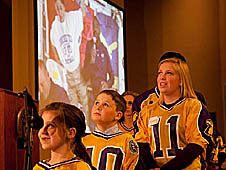 Three students wearing gold and purple football jerseys