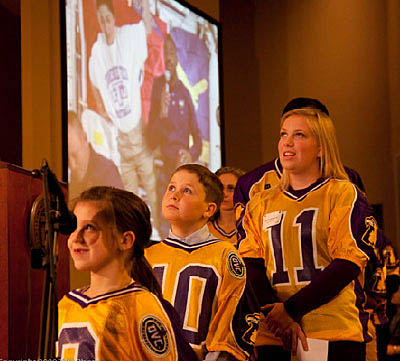 Three students wearing gold and purple Tennessee Tech football jerseys
