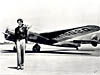 Amelia Earhart stands next to an airplane