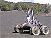 A small, four-wheeled robot in the desert