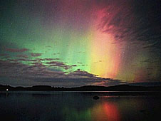 A red, yellow and green aurora display fills the night sky