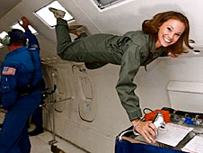 Emily Calandrelli smiles as she floats aboard an airplane