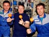 Three astronauts with oranges floating in front of them
