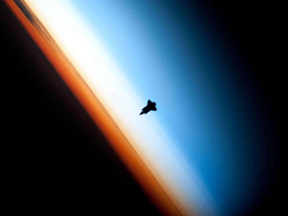 image of shuttle shilouetted against Earth