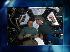 Astronauts Terry Virts and Stephen Robinson work inside the cupola.