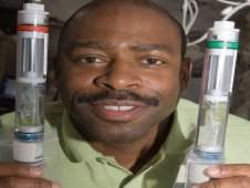 Astronaut Leland Melvin holding the Kennedy Space Center Fixation Tubes, KFTs, containing a TAGES harvest.