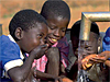 Children drink from an outdoor faucet