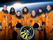 The STS-131 crew poses in orange suits in front of a picture of Earth