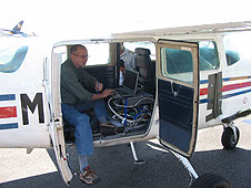 Dr. Tim Griffin works on leak detector in airplane.